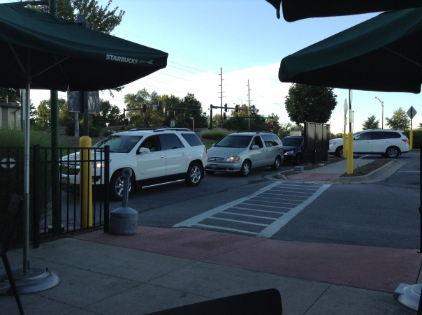 A long line of cars waiting to order their coffee from a Starbucks drive-through